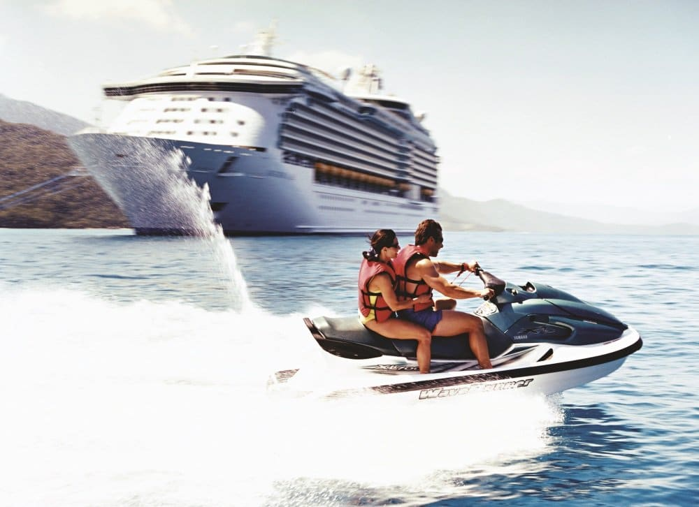 Couple jetskiing, jet skiing, sking, jetski, jet ski near Navigator of the Seas?, exterior in Labadee? Haiti with ship exterior in background, Caribbean, shore excursion, Voyager class, NV, man, woman