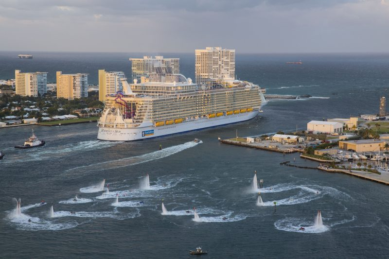 HM, aerials, Three Sisters event, Harmony of the Seas sails on maiden voyage out of Port Everglades, Fort Lauderdale, Nov 5, 2016, rear view, starboard side, port buildings, ocean view in background, flotilla send-off, team of 16 jetboard and jetpack riders from Aquafly Hydroflight Sports Performance Team,
